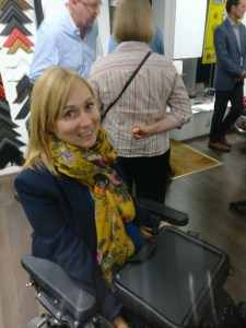 Clare Edwards inventor of the trabasack wheelchair tray using it at a private view at a gallery