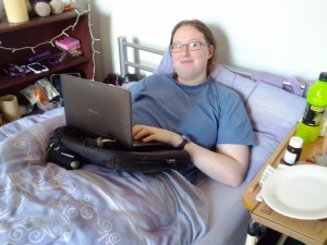 A person in bed using a trabasack curve as a bed tray for a laptop