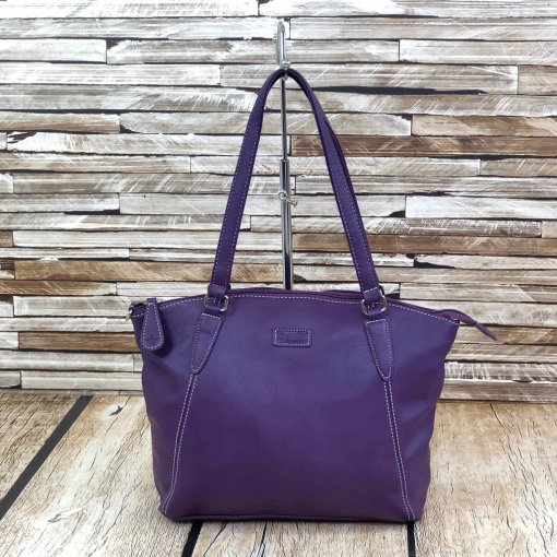 Image of a large ladies shoulder bag in a bold purple colour in front of and atop of a wooden background