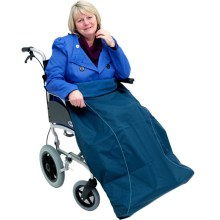 Image is a photograph of a middle-aged lady with bobbed blonde hair, sat in a wheelchair with a navy blue wheelchair leg protector