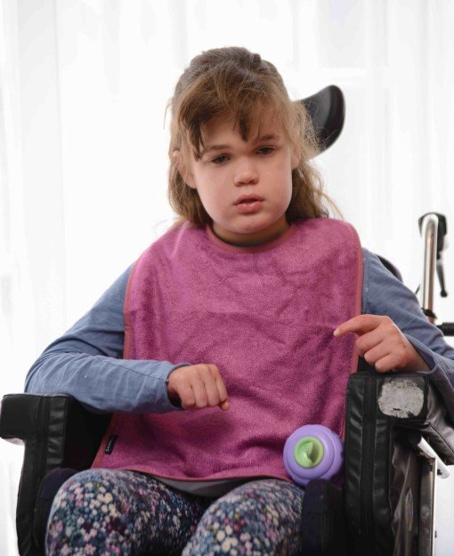 Image shows a photograph of a young girl sat in a wheelchair, wearing pretty floral leggins and a pink Seenin bamboo apron