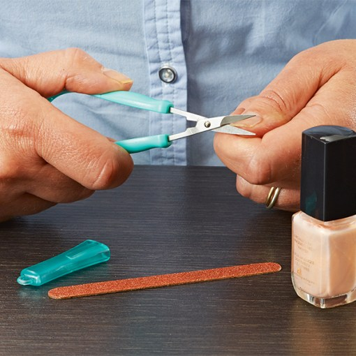 Image is a photograph of someone using the mini easi-grip scissors to trim their nails, with a bottle of nail varnish and a nail file on the table in front of them.