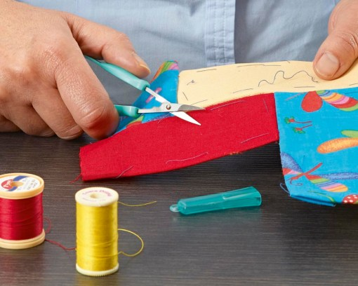 Image is a photograph of someone using the mini easi-grip scissors to cut through fabric for sewing.
