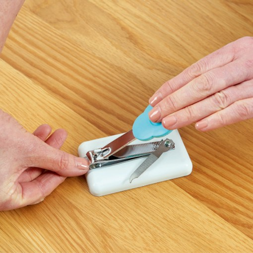 Image is a photograph of the easi-grip nail clippers on a wooden table top with one hand applying pressure to the padded lever, whilst a thumbnail is clipped on the opposite hand