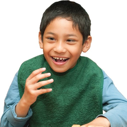 Image shows a photograph of a young boy, smiling with his hand raised, wearing a Racing Green coloured cotton apron