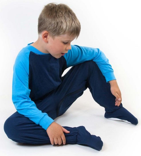 Image shows a photograph of a boy seated casually on a white background, wearing a footed sleepsuit in navy and turquoise