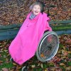 Image shows a photograph of a young girl in an outdoor, autumnal setting, laughing whilst sat in a wheelchair wearing a fuchsia total cover fleece