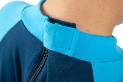 Image shows a photograph of the back of a boy's neck, wearing the Seenin sleepsuit in navy and turquoise, to illustrate the hidden zip area