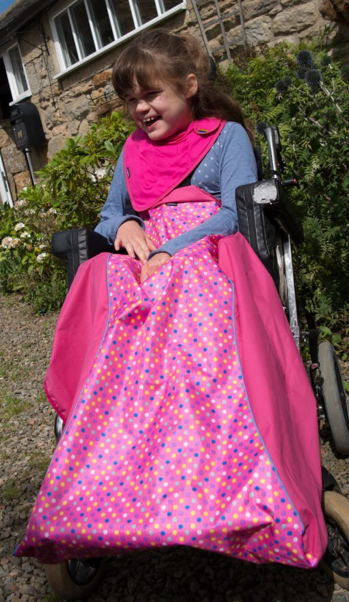 Image is a photograph of a young brown-haired girl laughing, whist sat outside a stone house in a wheelchair, wearing pink spot wheelchair leg cover