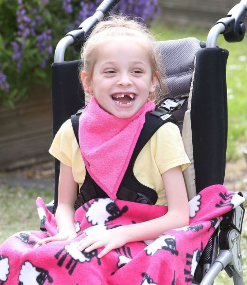 Image shows a photograph of a laughing young girl, sat outside in a wheelchair, wearing a bright pink kerchief around her neck with a pink sheep-patterned fleece blanket upon her knees.
