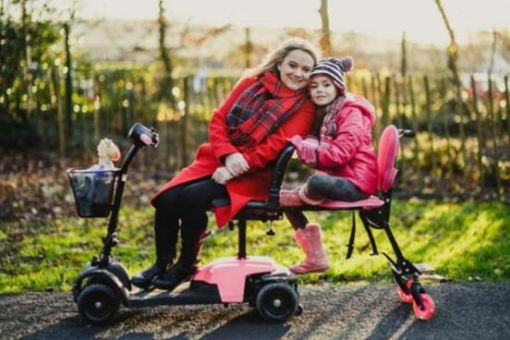 Image is a photograph of a mum sat outdoors in the countryside, sideways in a mobility scooter, smiling with her head resting gently against the head of her daughter, who is sat behind her on a Skoe Hitch trailer in pink.