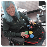 Image is a photograph of Sasha using the Curve Connect to play video games using switches and a joystick