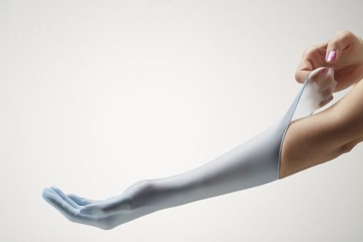 Image is a photograph of a forearm outstretched, wearing a blue nitrile medical glove, with the opposite hand pulling the cuff of the glove upwards towards the torso to demonstrate the elasticity and strength of the glove