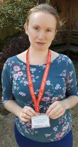 Image is a photograph of a brunette woman in a floral top, stood outdoors wearing a 'Social Distancing' ID and red lanyard