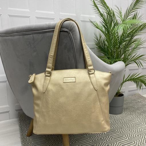 Image is a photograph of a Gold Samantha Renke accessible handbag in the extra size, hanging by the straps over the back of a grey velvet chair in a living room.
