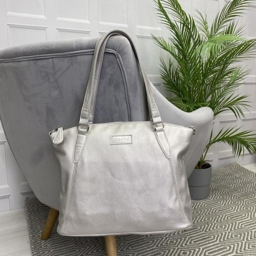Image is a photograph of a Matt Silver Samantha Renke accessible handbag in the extra size, hanging by the straps over the back of a grey velvet chair in a living room.