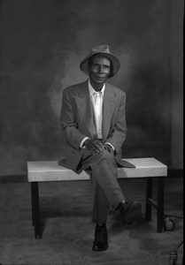 Portrait of Eugene Freeman Shake Oliver, a shoe shiner in Dublin, Texas, wearing a suit and hat.
