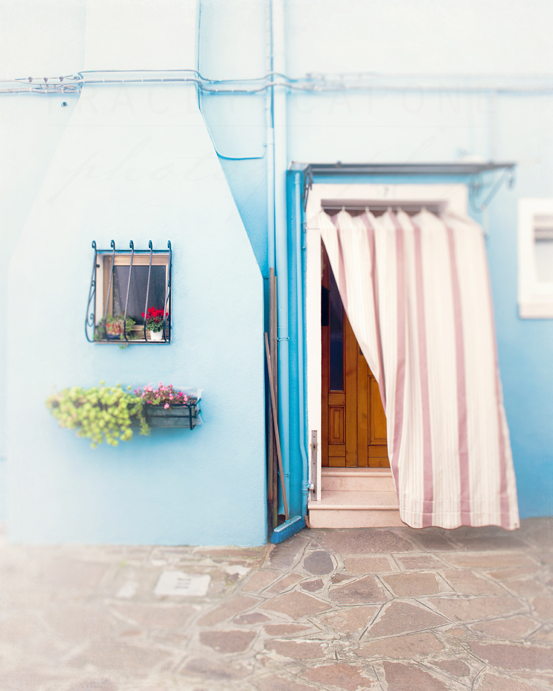 Photograph of a blue house with a pink and white curtain on the island of Burano, near Venice. Photograph by Chicago artist Tracey Capone.