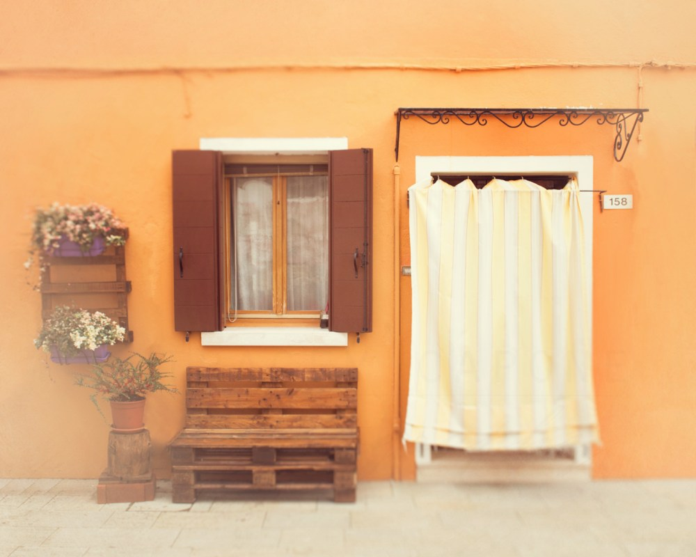 Bright orange home with yellow and white curtain on the island of Burano, Italy. Travel photograph by Tracey Capone.