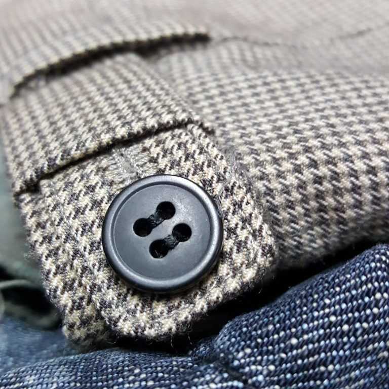 Undertaking clothing repairs with button sewn back on