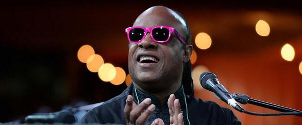 vencedores do grammy Stevie Wonder usando um óculos escuro rosa, uma jaqueta de couro, o microfone perto do seu rosto e aplaudindo