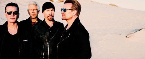vencedores do grammy vivos u2 vencedores do grammy em um deserto e todos usando uma camiseta e jaqueta preta o vocalista, Bono, está de perfil e usando um óculos escuro