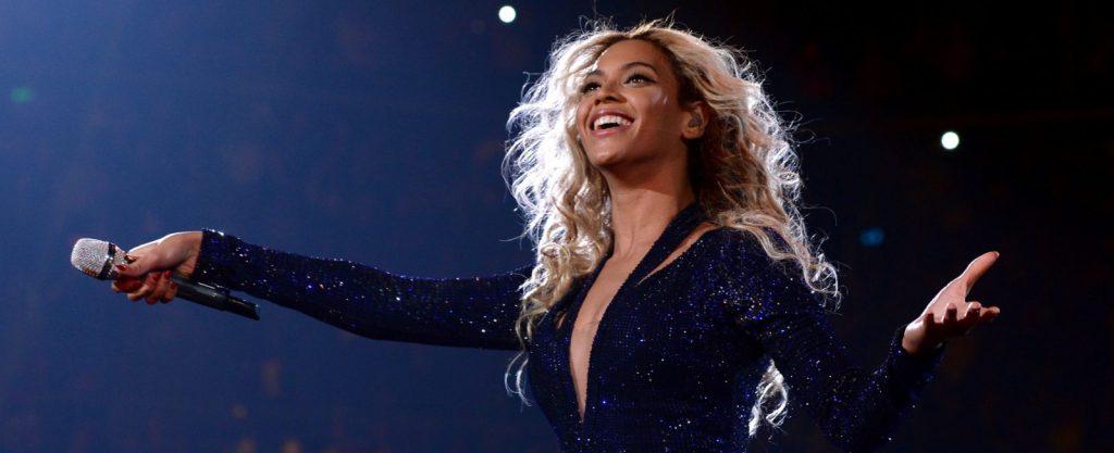 """A imagem apresenta a cantora Beyoncé. Ela está em um show ao vivo, vestindo um colante azul marinho. A cantora, loira, olha para cima, enquanto põe o microfone para a plateia cantar. A imagem destaca a matéria: """"Beyoncé, Taylor Swift e outras 3 inspirações para artistas da nova geração""""."""
