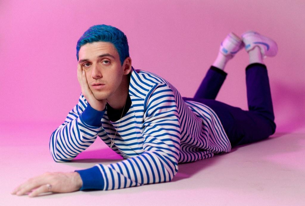 A imagem tem como destaque o cantor Lauv, num ensaio fotográfico para sua nova turnê. O cantor está destaque com uma roupa e cabelo azuis, e um fundo completamente rosa.
