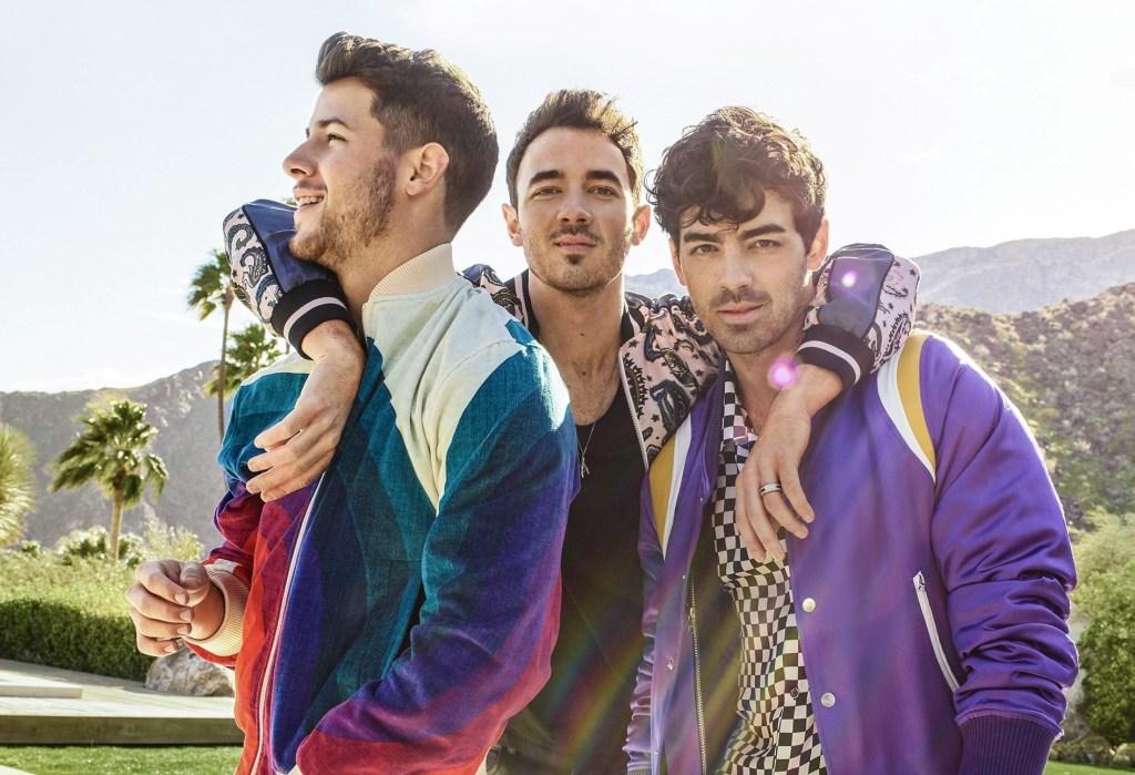 os jonas brothers juntos e logo atrás colinas. Joe Jonas usa um casaco roxo e uma quadriculada preta e branca; Nick Jonas usando um casaco colorido e está de perfil e Kevin Jonas usa um casaco azul e bege com estampa e uma blusa preta por baixo