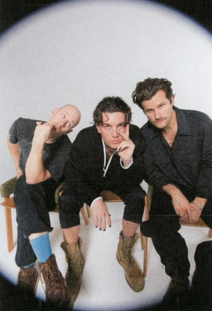 Da esquerda para a direita: Les Priest, Paul Klein e Jake Goss. integrantes do LANY. Os cantores estão sentados em cadeiras num fundo branco.