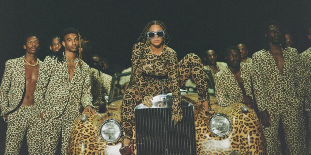 """Beyoncé no ensaio fotográfico para """"Black Is King"""". A cantora aparece no capô de um carro estampado, e vários dançarinos rodeiam o veículo. Todos usam roupas com estampa de onça."""
