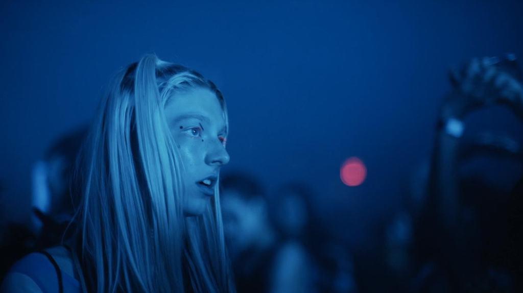 Jules, personagem de Euphoria, olhando para algo fora da imagem com uma expressão de quem não acredita no que vê, Ela usa maquiagem nos olhos, tem algumas mechas dos cabelos presas e toda a imagem é de uma luz azul.