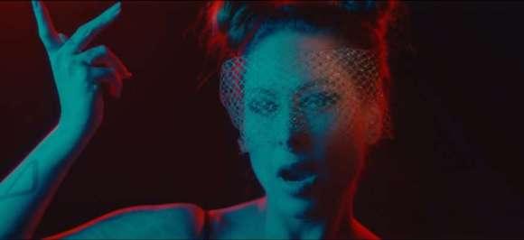 Na foto, Pitty, no clipe de Na Tela, está em um ambiente escuto e usa uma tela de tecido tampando os olhos