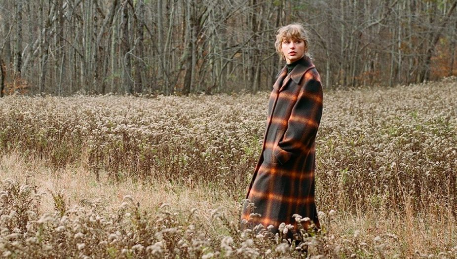 taylor swfti em meio a um campo e árvores ao fundo imagem de divulgação do album evermore de taylor swift