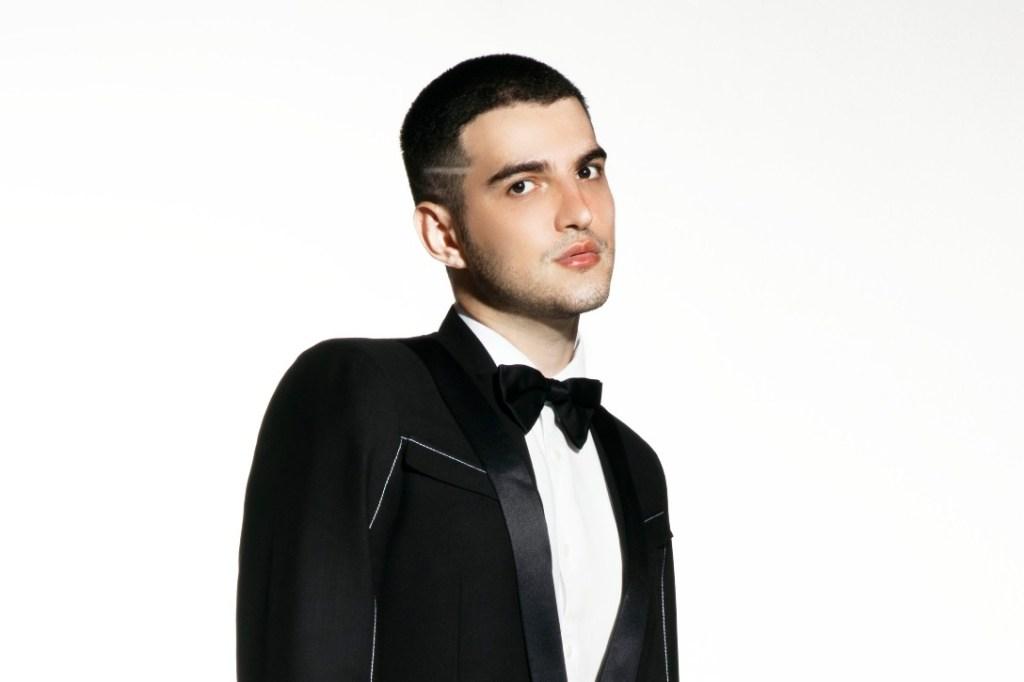 """Em uma imagem promocional de seu novo single """"Coringa"""", Jão aparece vestido com um terno e uma gravata borboleta, levemente virado para a direita e com a cabeça erguida enquanto olha para a frente."""