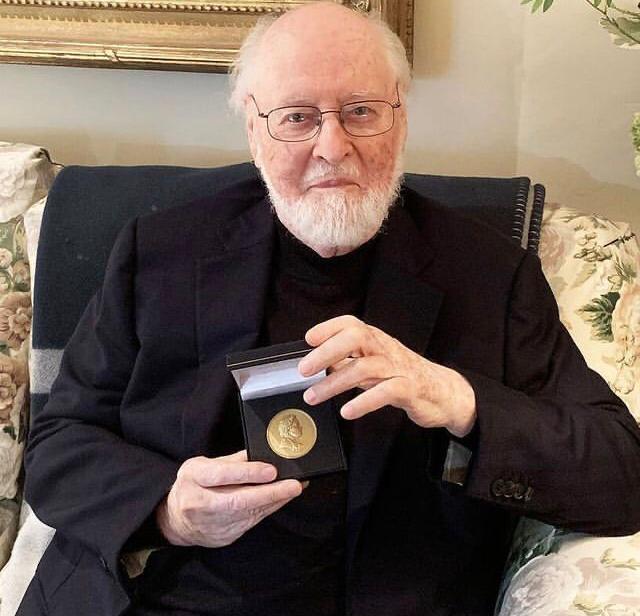 um dos maiores vencedores do grammy, John Williams está usando um terno preto, sentado em um sofá com almofadas floridas e segurando uma medalha de ouro
