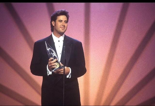 vencedores do grammy vince gill usando um terno preto e camisa branca por baixo, segurando um prêmio e falando no microfone