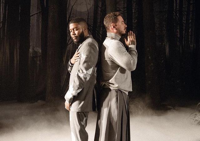 """J Balvin e Khalid no clipe de """"Otra Noche Sin Ti"""" usando roupas cinzas, com uma fumaça branca no chão em meio a uma floresta sombria."""