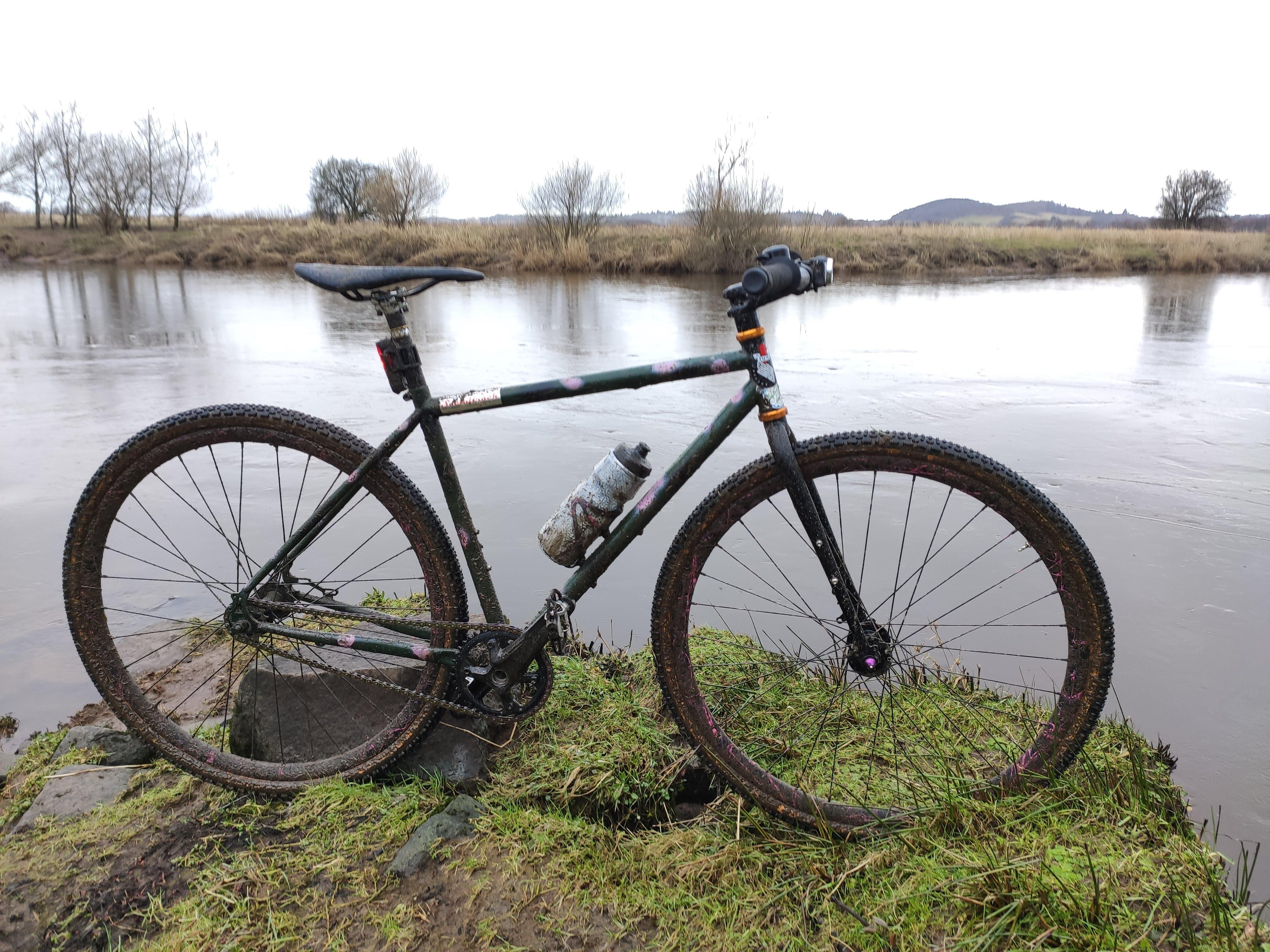 muddy tracklocross bike by river