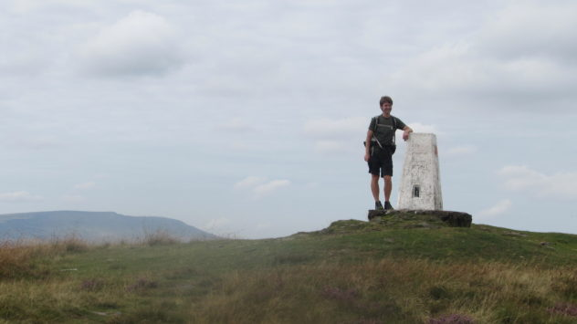 Harri Garrod Roberts at the trig point on the summit of Fan Frynych, Fforest Fawr, Brecon Beacons National Park, Wales