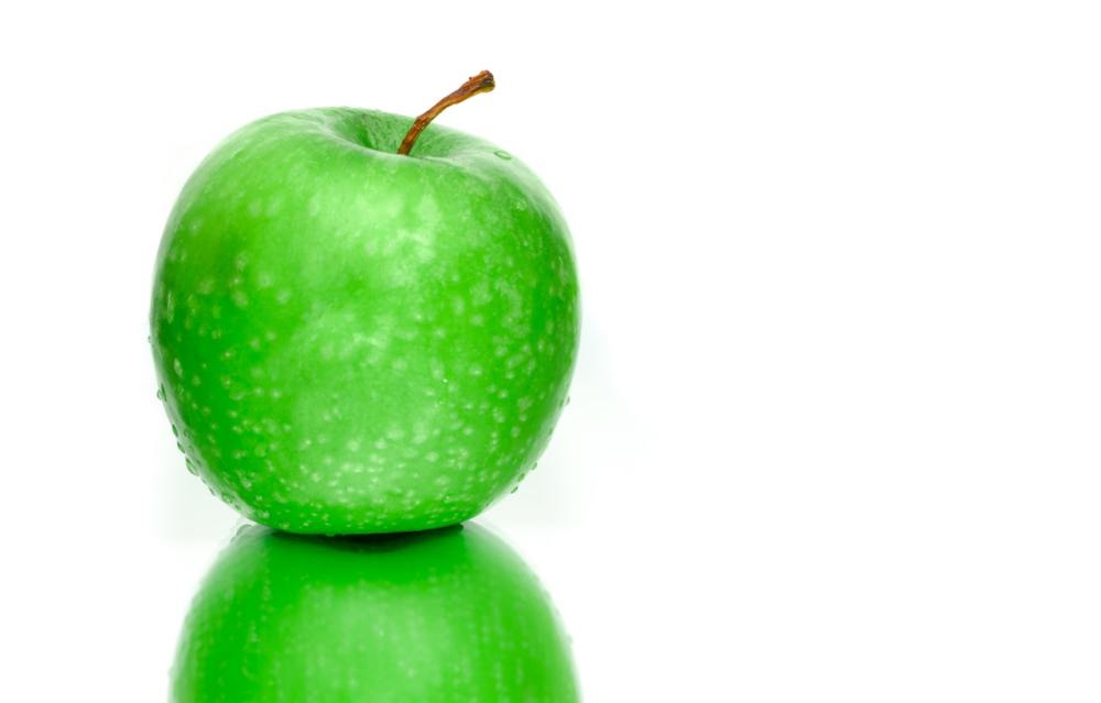 Green apple on reflective surface