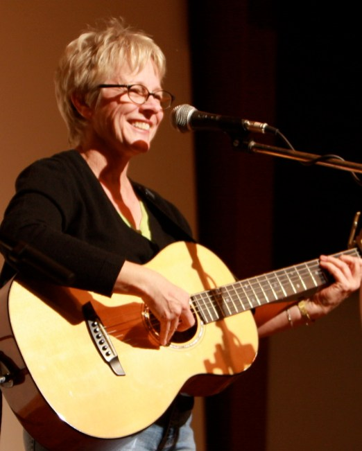 photo of Tracy Newman standing on stage with acoustic guitar at Folktacular 2008