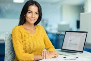 woman in yellow blouse with laptop