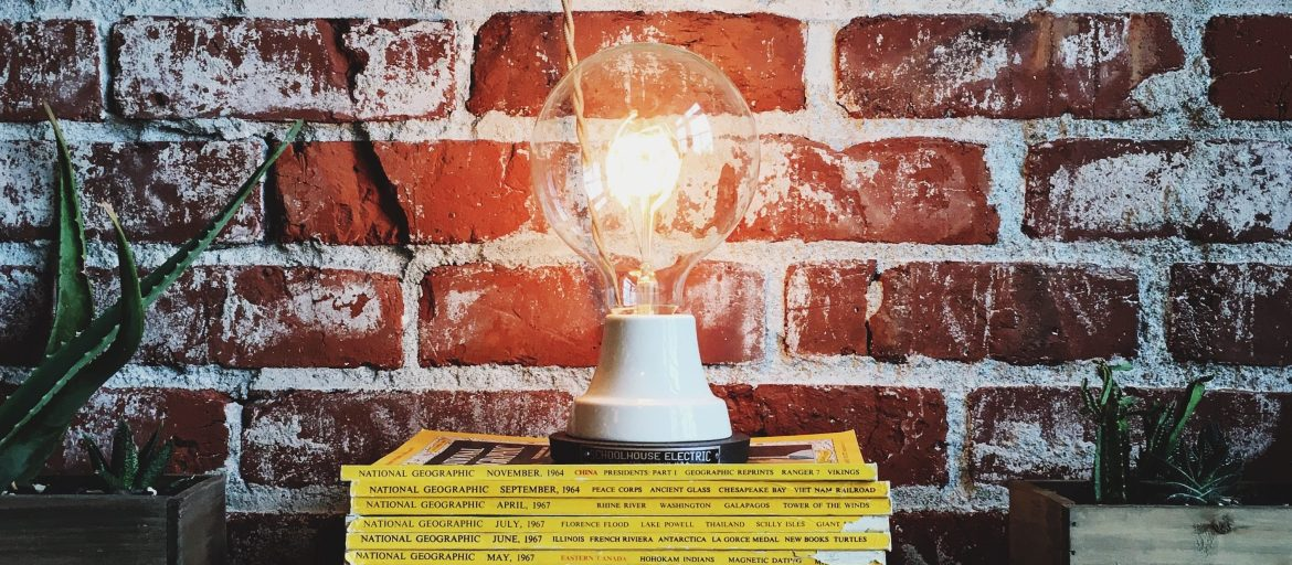 A glowing lightbulb sitting on a stack of books.