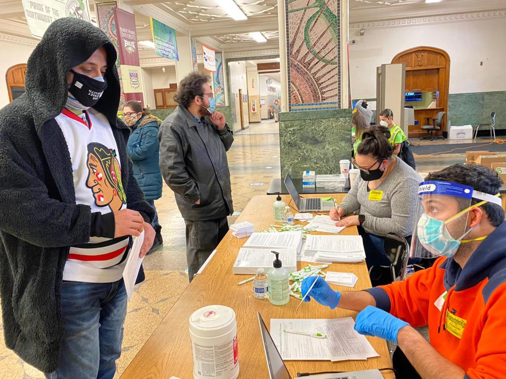 A man in a Chicago Blackhawks hockey jersey signs in at a registration table at a vaccine clinic in a school hallway.