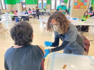 A woman gives a COVID-19 vaccine to a member of the Belmont Cragin community in Chicago at Steinmetz High School