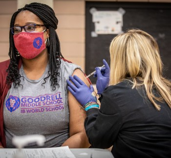 A woman wearing a gray t-shirt from Goodrell Middle School gets a COVID-19 vaccine shot from another woman