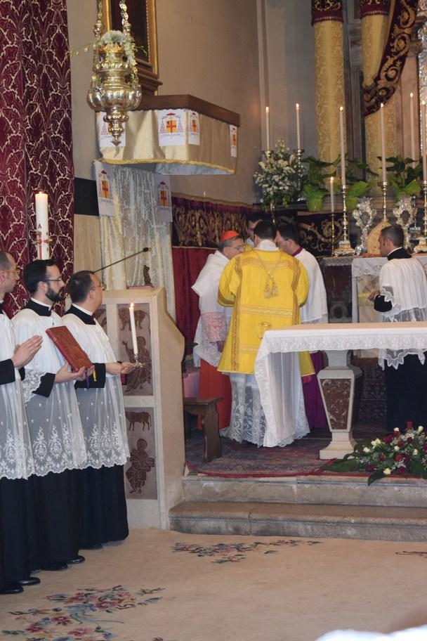 Započinje oblačenje biskupa: prvo se oblači amikt. Svaki dio ruha oblači se uz prigodnu molitvu.
