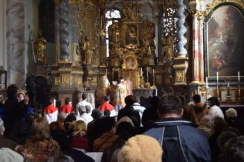 """Pjevanje Sanctusa. Ispred oltara su prisutna petorica ministranata, od kojih jedan nosi stijeg s izvezenim natpisom """"Sanctus""""."""