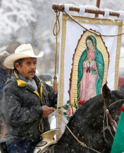 A member of of Club Los Vaqueros Unidos (United Cowboy Club) of Wadsworth, Ill., carries a banner of Our Lady of Guadalupe as he makes his way to the the Shrine of Our Lady of Guadalupe in Des Plaines, Ill., as part of a pre-celebration for her Dec. 12 feast day. The feast celebrates the appearance of Mary to indigenous peasant St. Juan Diego in 1531 near present-day Mexico City. (CNS photo/Karen Callaway, Catholic New World) See GUADALUPE-RIDERS-SHRINE Dec. 7, 2016.